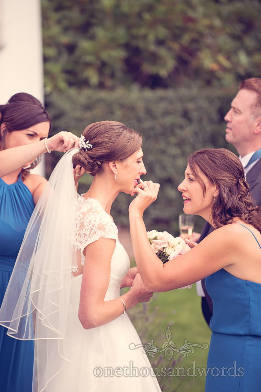 Bridesmaids help bride with lipstick and veil at Harbour Heights wedding
