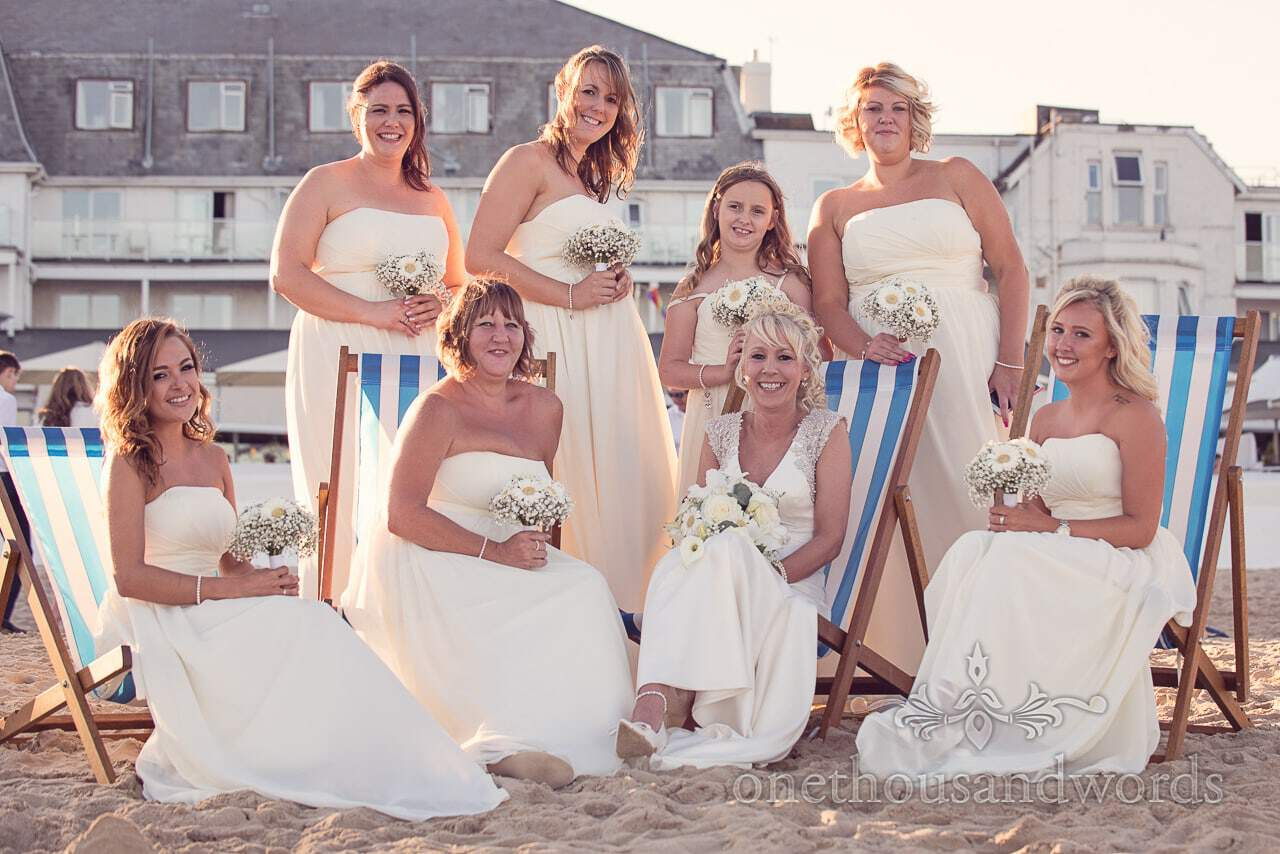 Bridesmaids in lemon coloured bridesmaids dresses on striped deck chairs on beach