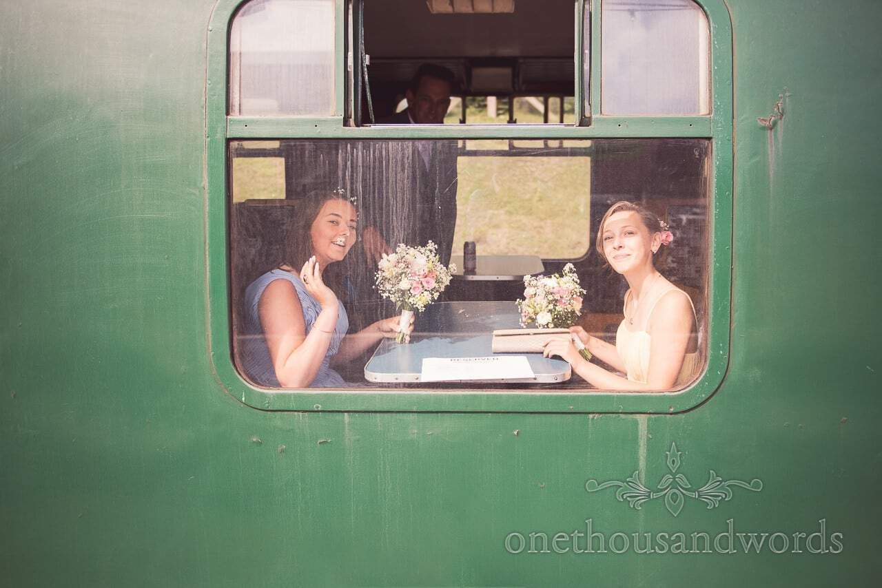 Bridesmaids with pastel wedding bouquets in green steam train carriage