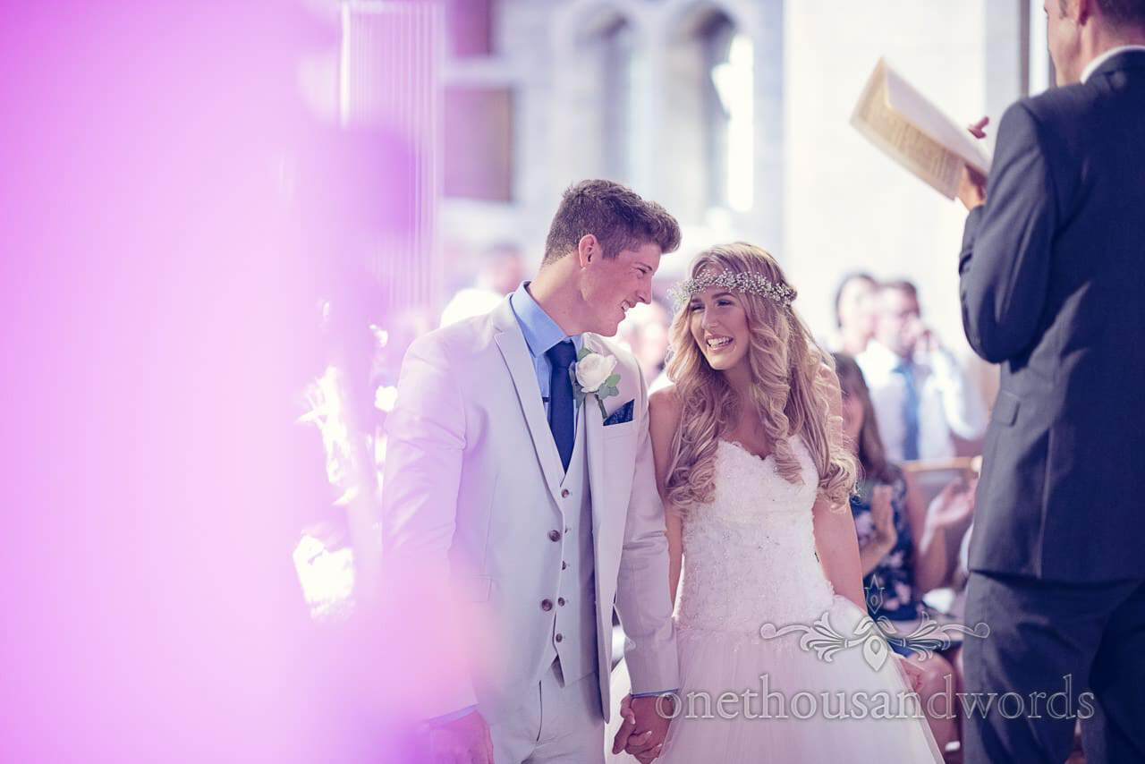 Cute bride and groom laugh together during Church wedding ceremony with purple lighting
