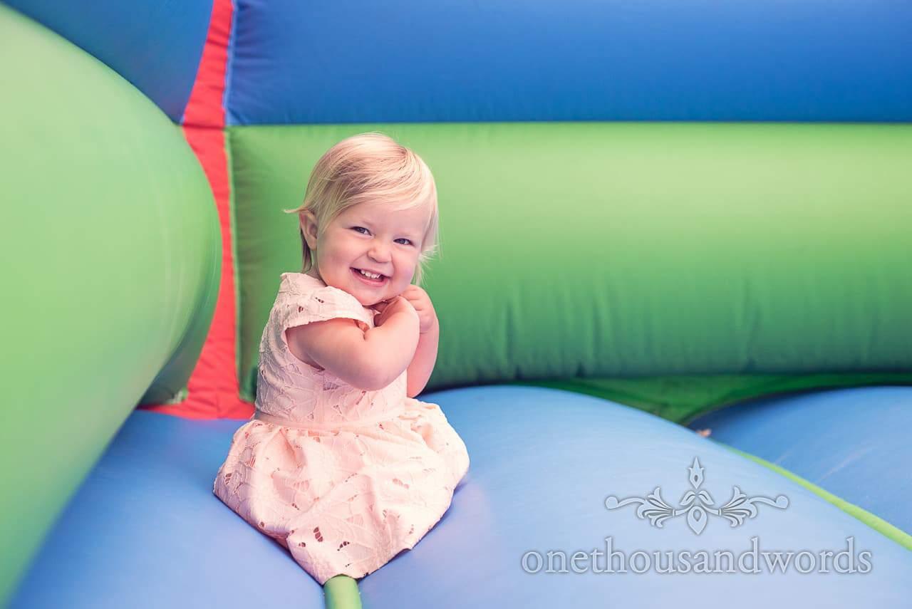 Cute child wedding guest on bouncy castle at Harmans Cross Village Hall Wedding