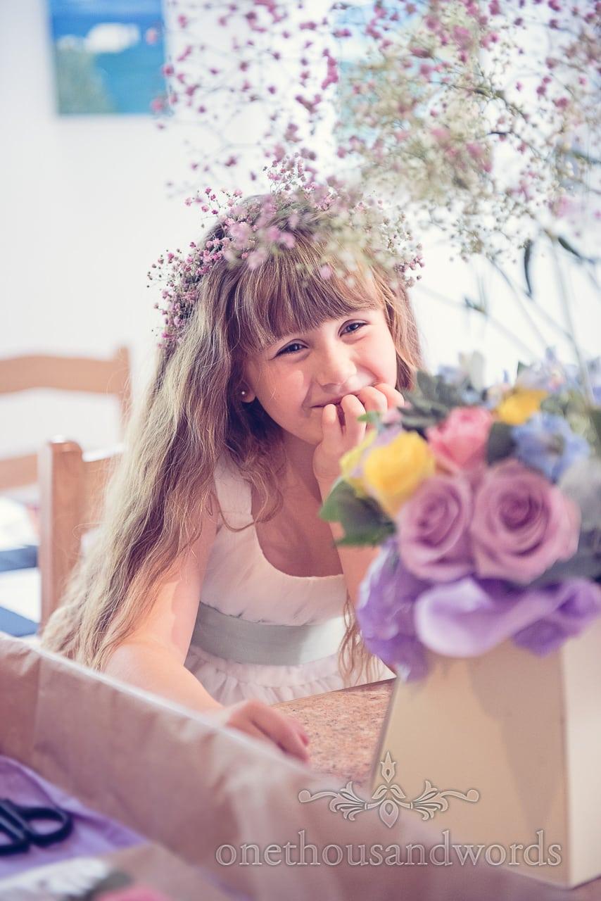 Cute wedding flowergirl with pink gypsophila headband looks at wedding flowers