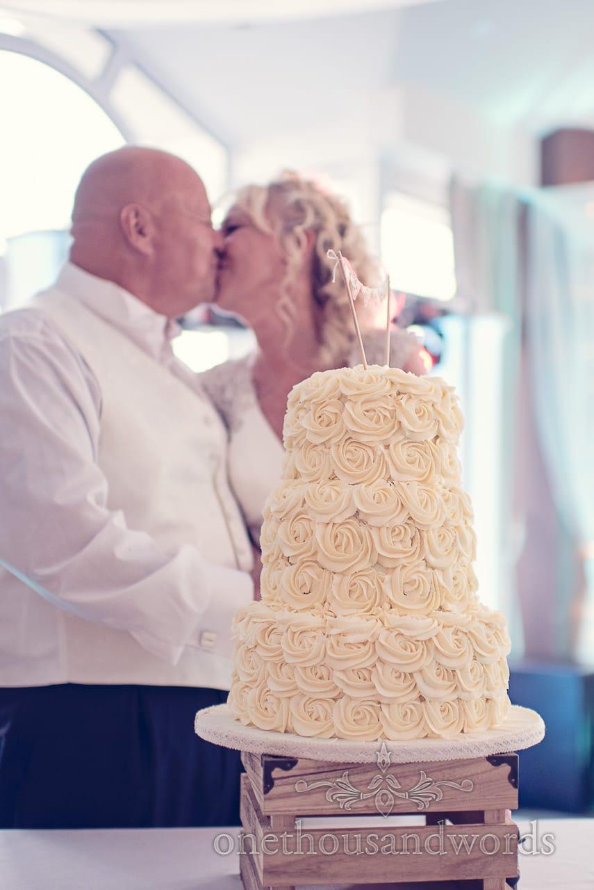 Cutting the cake with three tier cream coloured wedding cake at Sandbanks Hotel