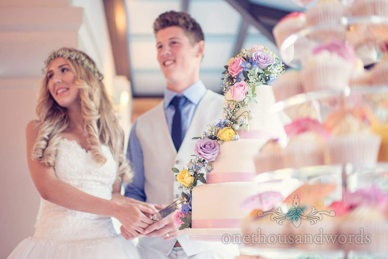 Cutting the wedding cake with pastel fowers at italian villa wedding photographs