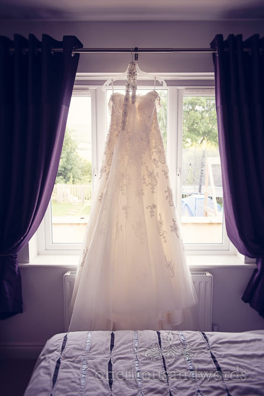 Detailed ivory wedding dress with diamantes hanging backlit in a window