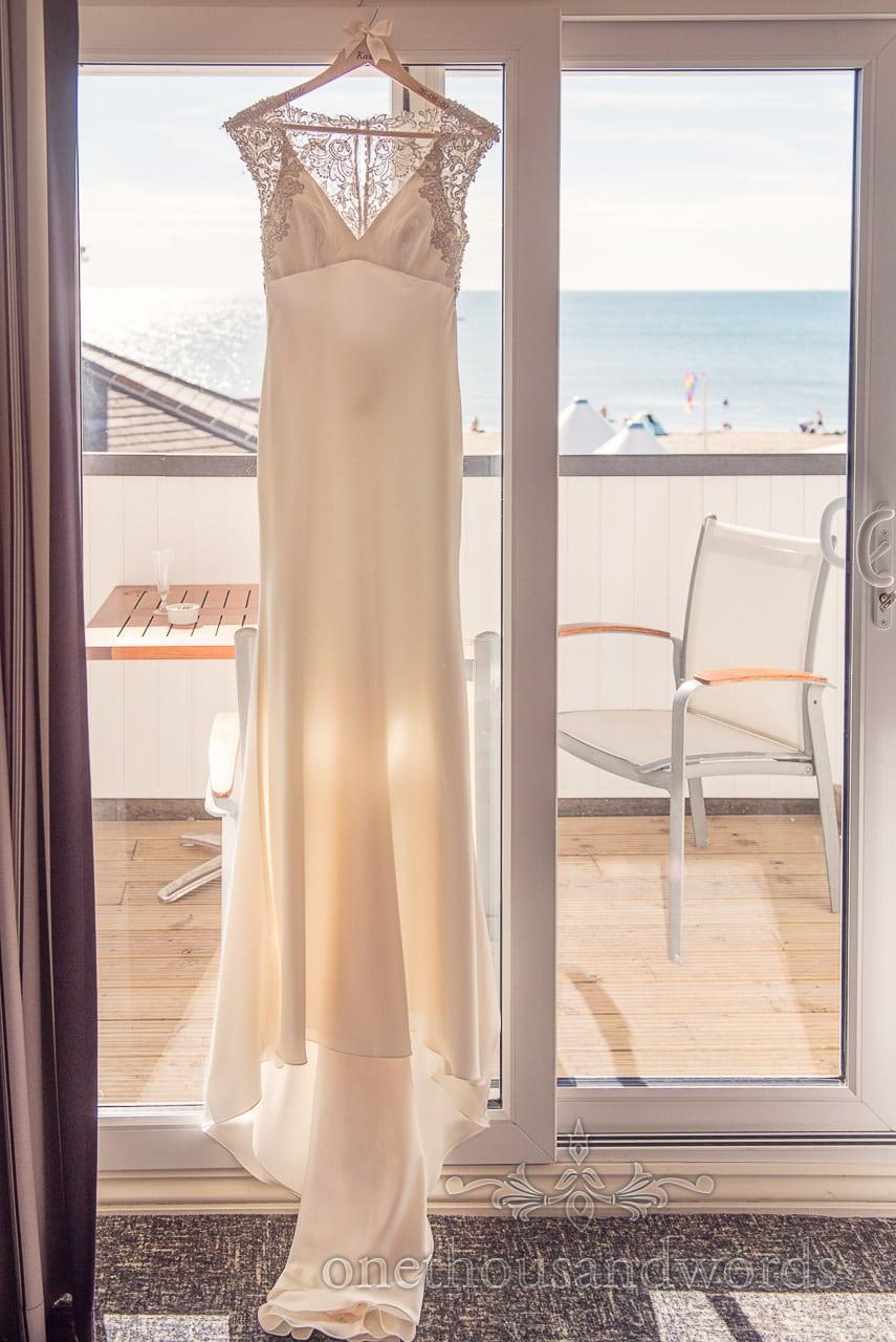 Dress hangs in the window from Sandbanks Hotel Wedding