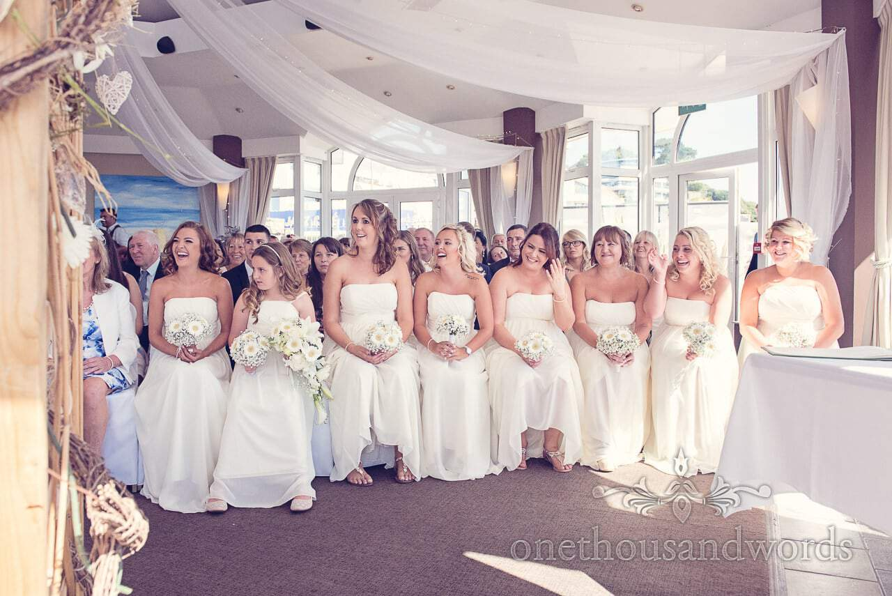 Eight bridesmaids in yellow at Sandbanks Hotel Wedding ceremony