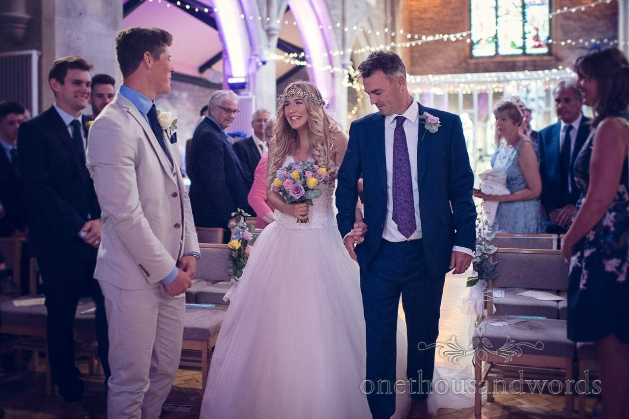 Father of the bride and bride walk down the aisle at church wedding ceremony