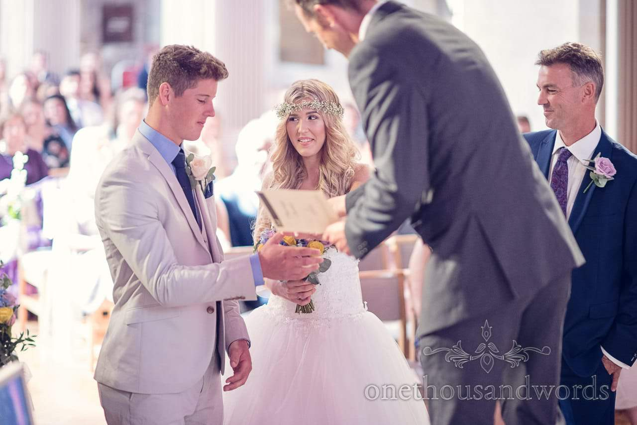 Father of the bride gives the groom his daughters hand in marriage in church wedding ceremony