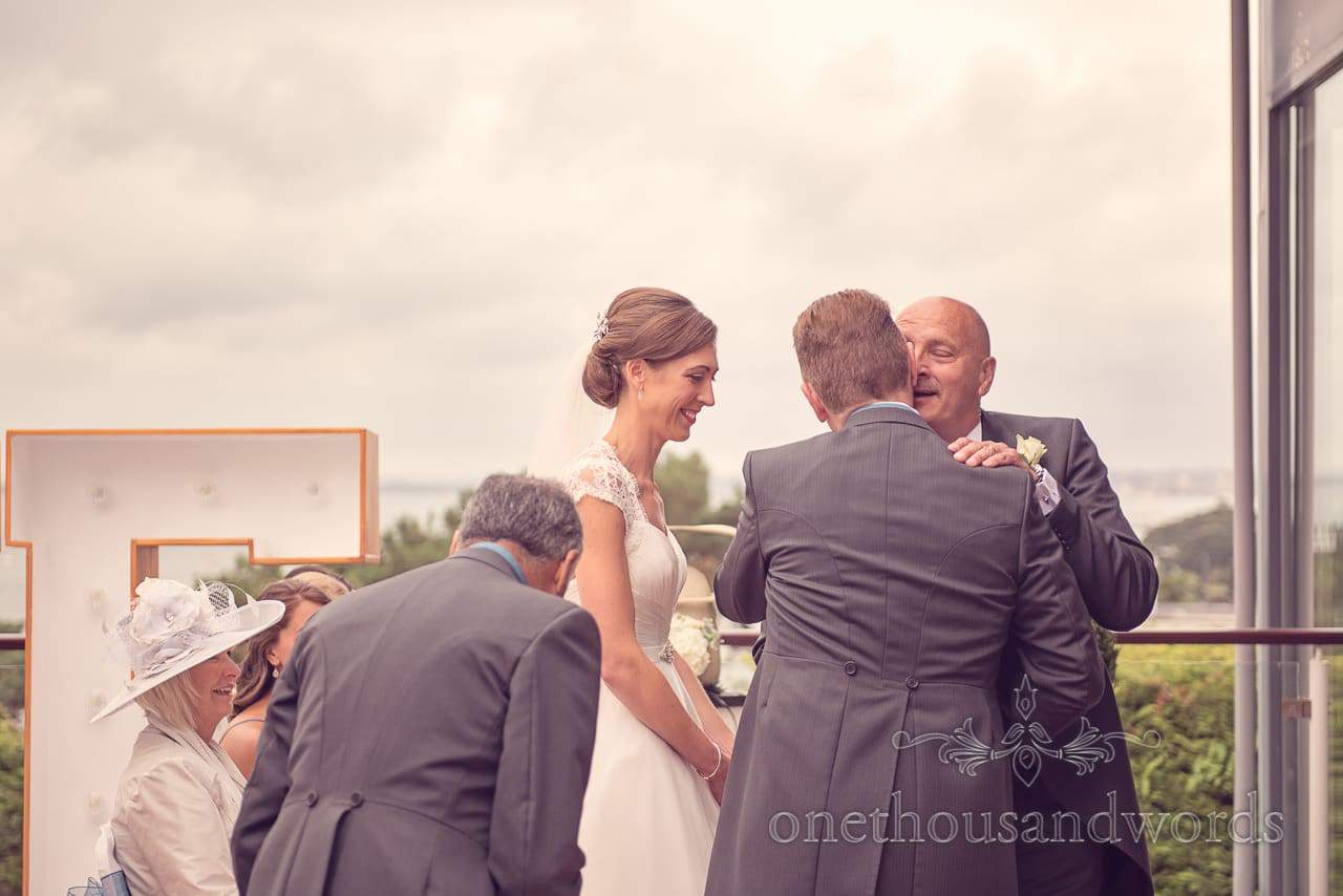 Father of the bride hands over the bride to the groom at Harbour Heights wedding photographs