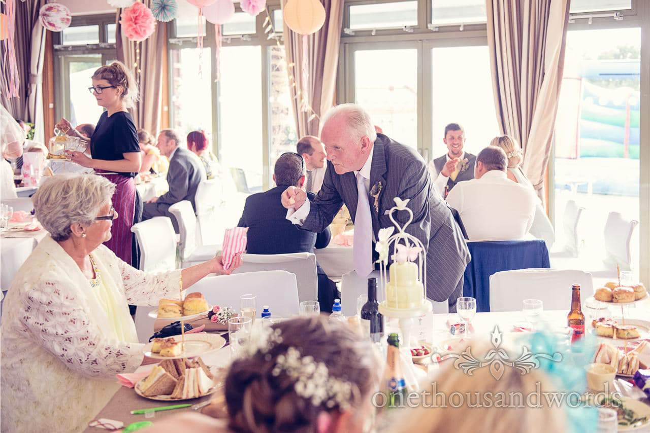 Father of the groom pinches a sweet at Harmans Cross Wedding