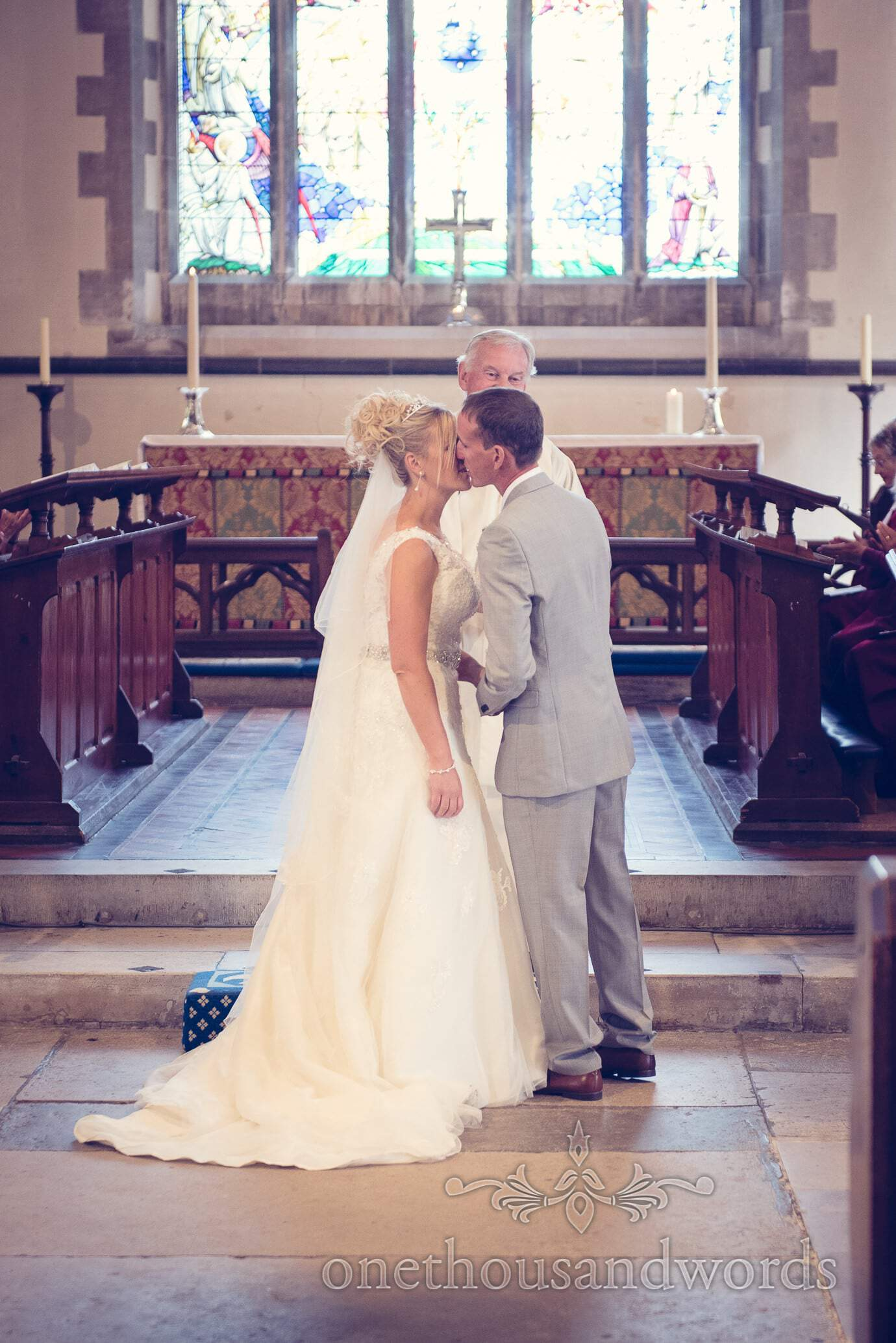 First kiss between bride and groom in Swanage church wedding ceremony