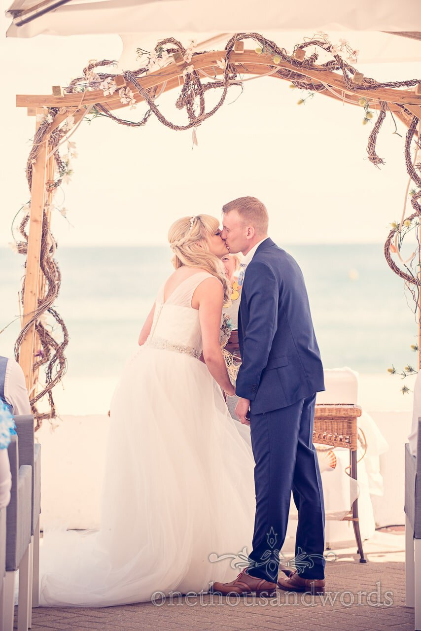 First kiss under seaside theme arbour at outdoor wedding ceremony by the sea