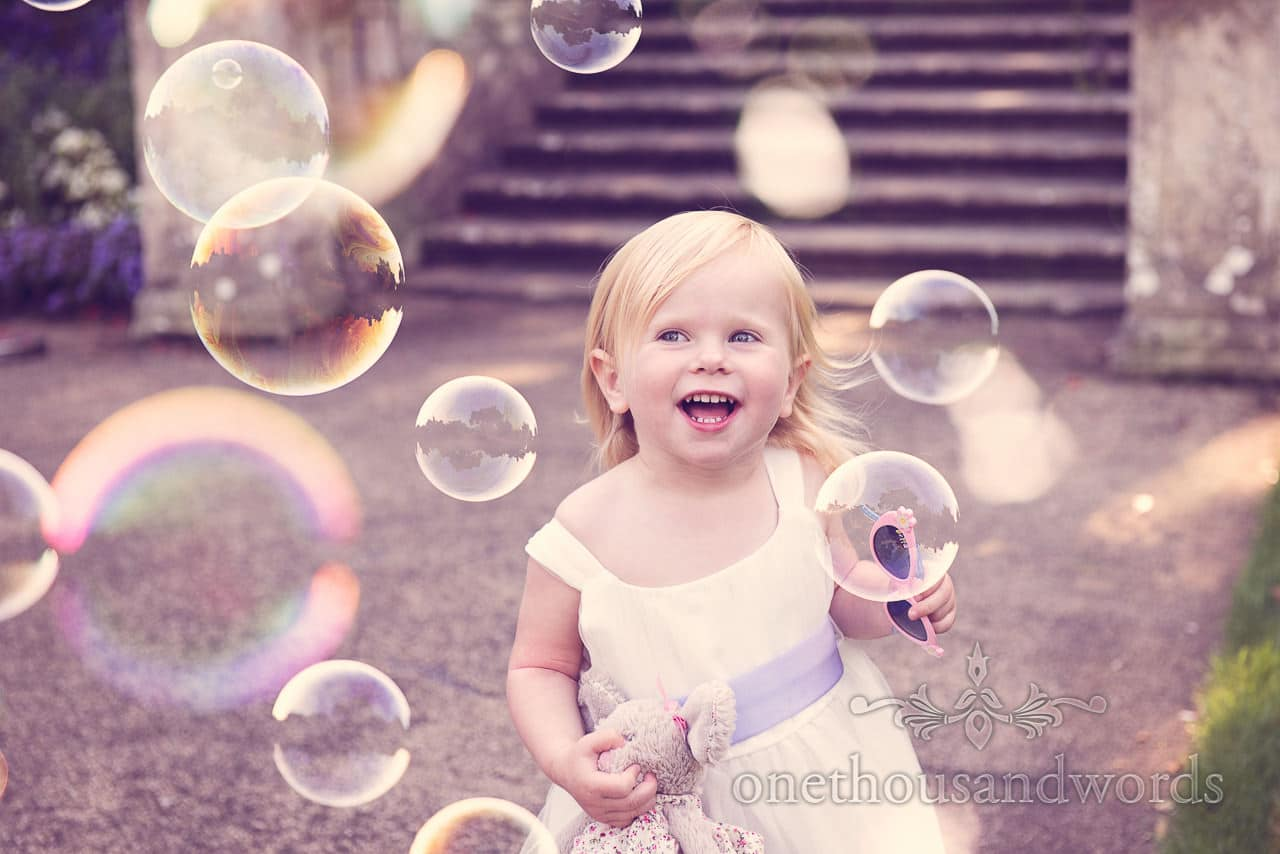 Flower girl plays with bubbles at italian villa wedding photographs