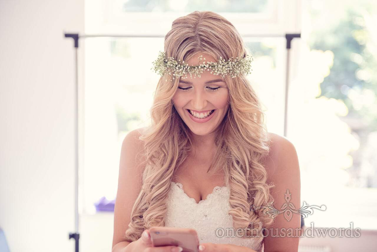Gorgeous blonde bride with gypsophila head band checks her phone on wedding morning