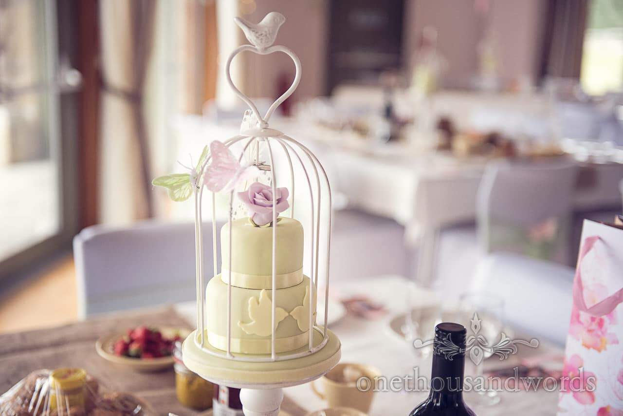 Green birdcage wedding cake with flower and butterfly decorations