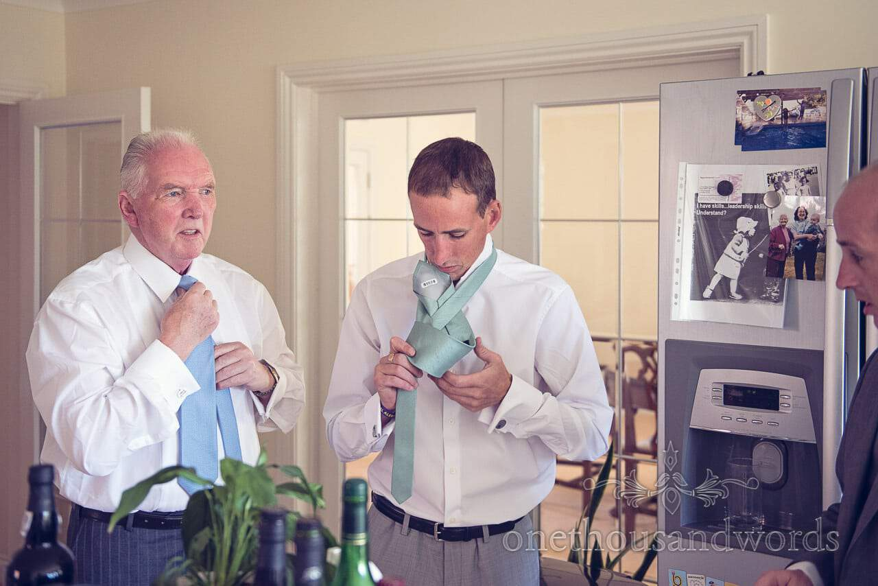 Groom and father of groom tie wedding ties on wedding morning in Swanage