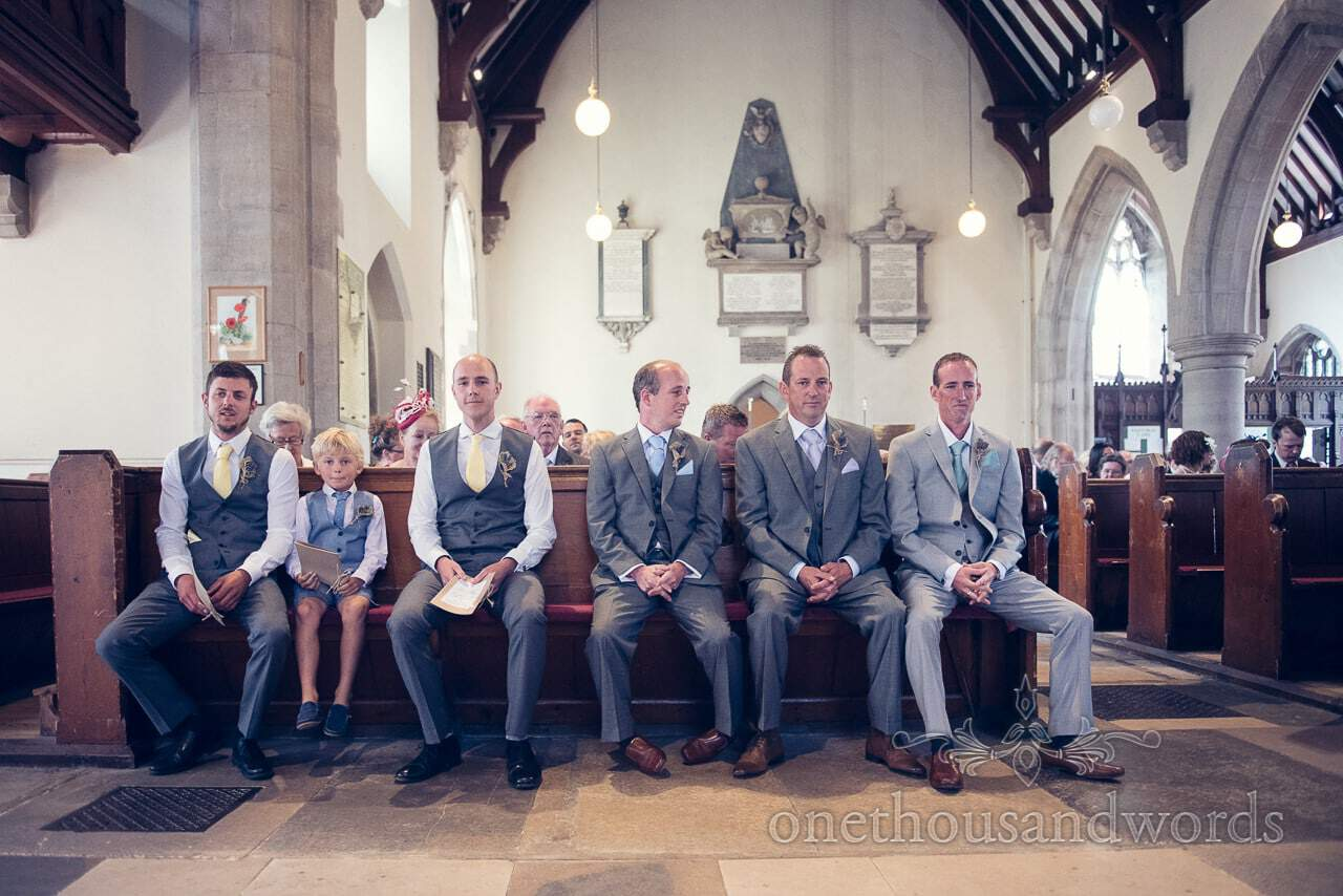 Groom and groomsmen in grey suits wait on church pew at Swanage church wedding
