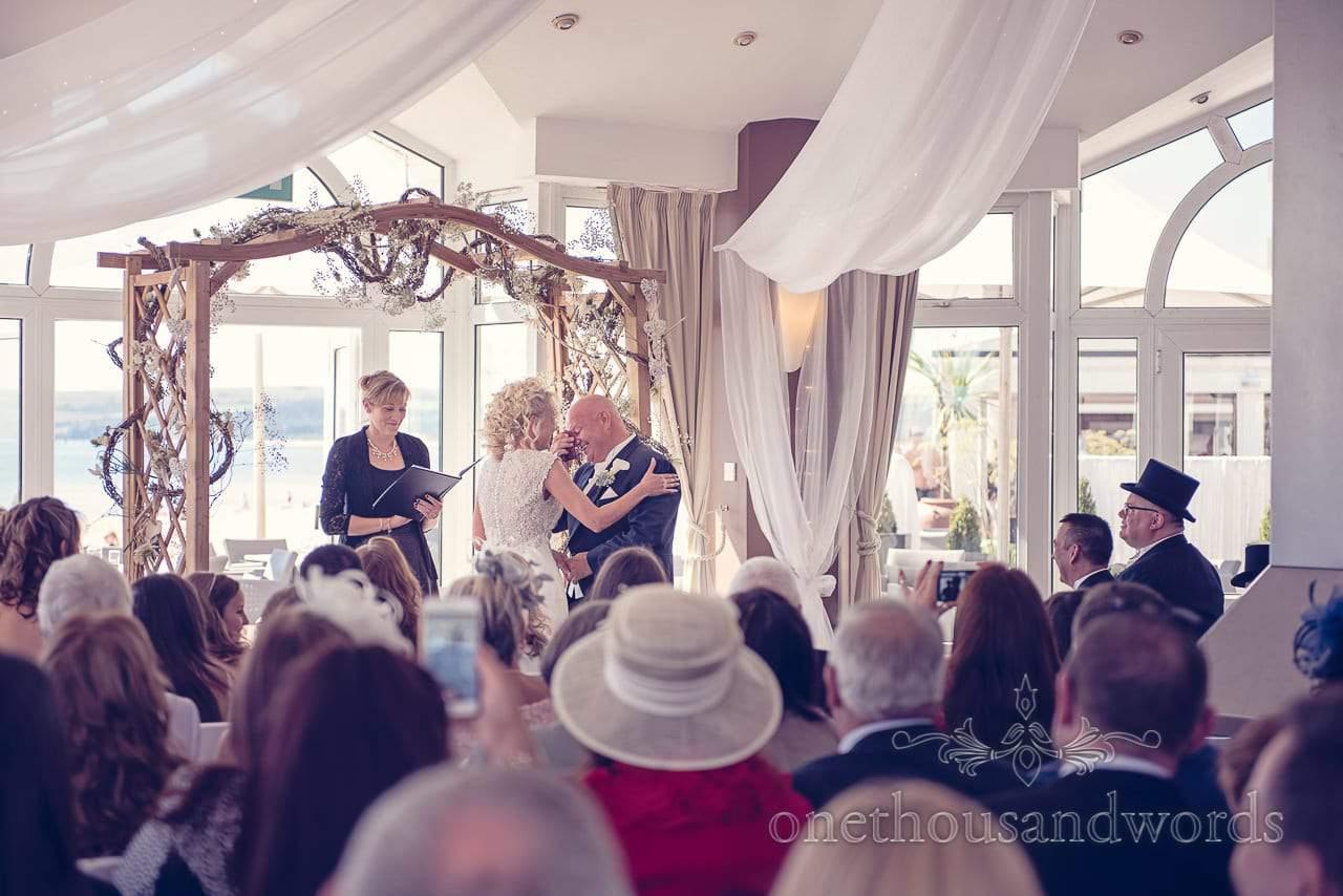 Groom cries under flower arbour at Sandbanks Hotel Wedding ceremony in Dorset