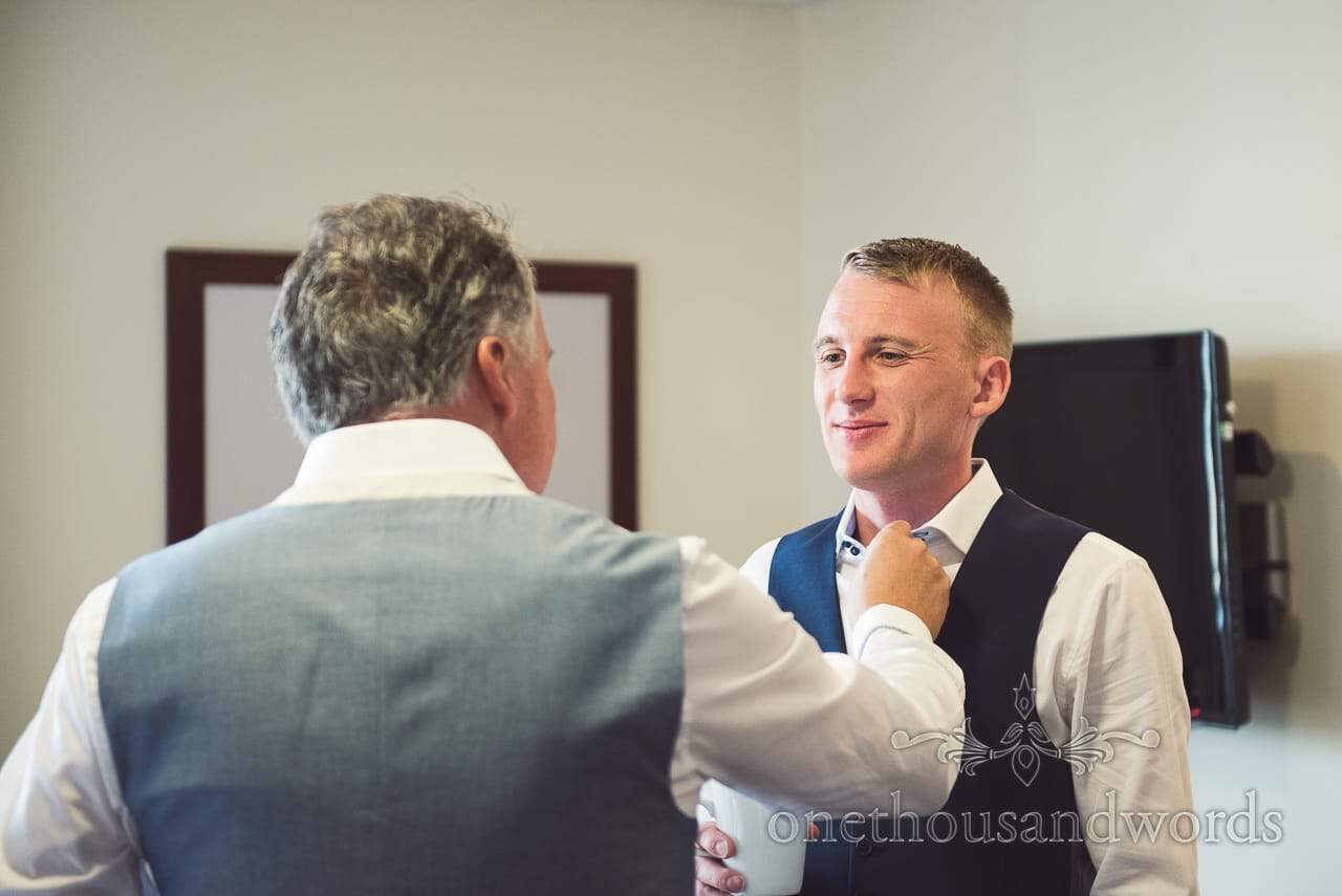 Groom has shirt styled by father on wedding morning at Sandbanks Hotel wedding