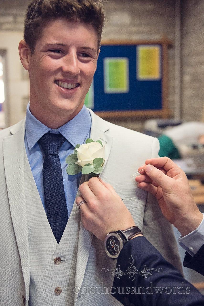 Groom has white rose wedding buttonhole flower added on wedding morning