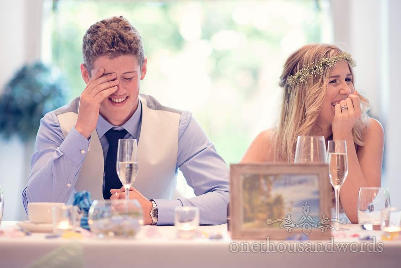 Groom holds head in hands during wedding speeches at italian villa wedding