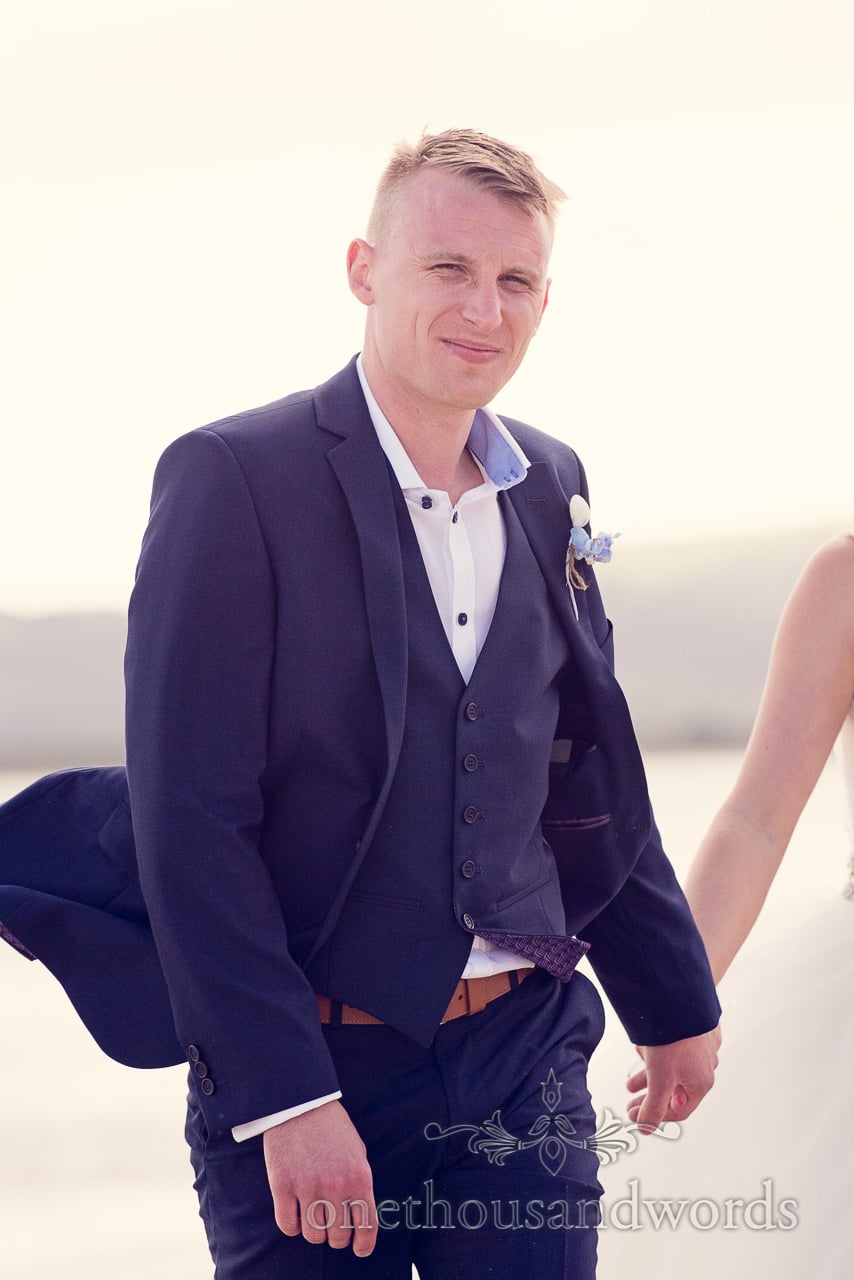 Groom in blue three piece wedding suit at seaside theme wedding photographs