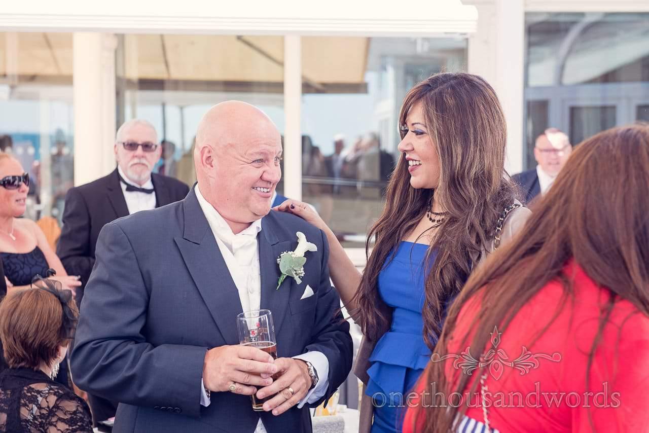 Groom in dark blue wedding suite greets wedding guests at Sandbanks Hotel