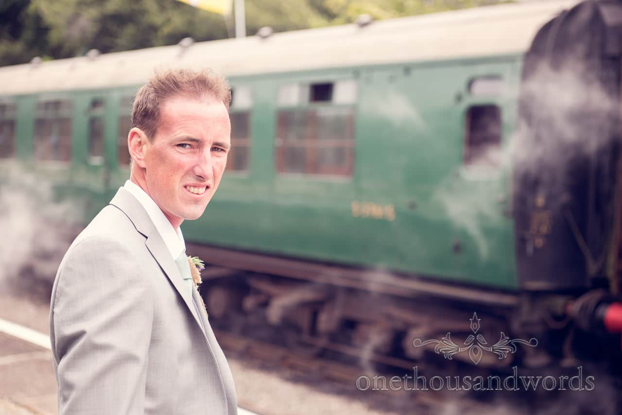 Groom in grey wedding suit portrait photograph with green steam train