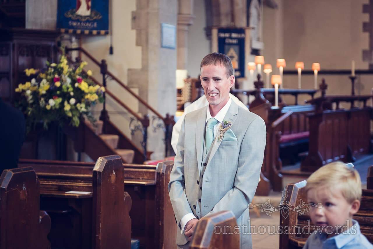 Groom in light grey wedding suit greets wedding guests at Swange Church wedding