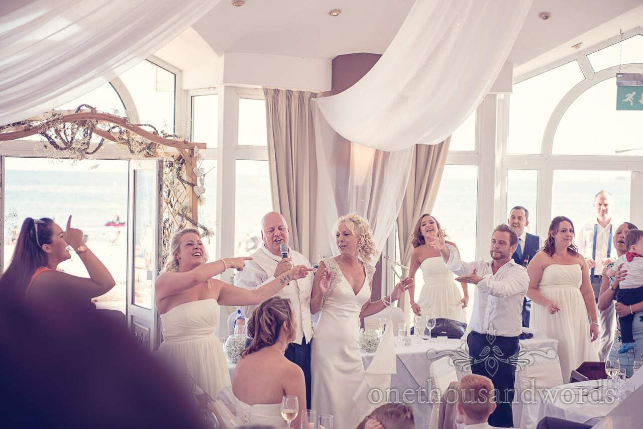Groom sings to music in the Compass suite at Sandbanks Hotel Wedding