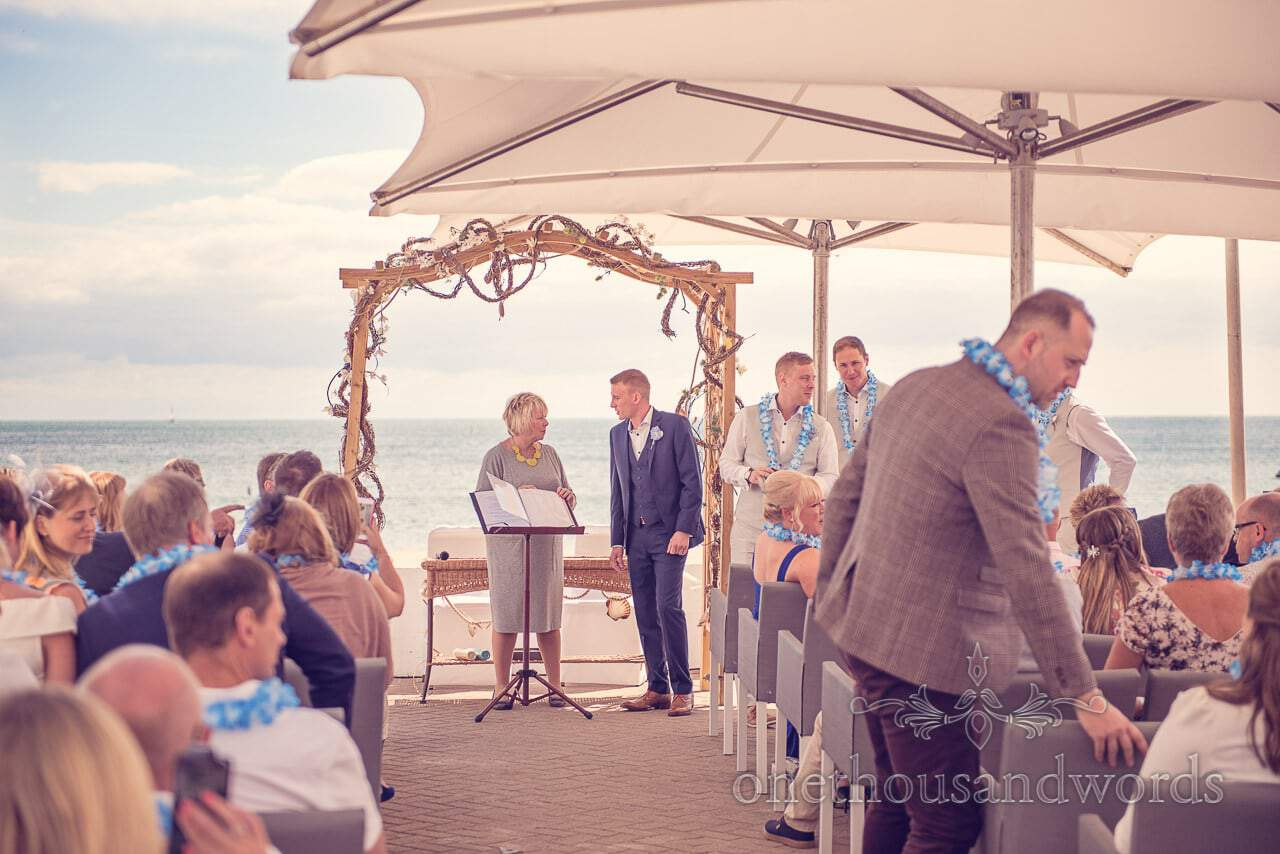 Groom talks to civil celebrant at outdoor seaside theme wedding in Dorset