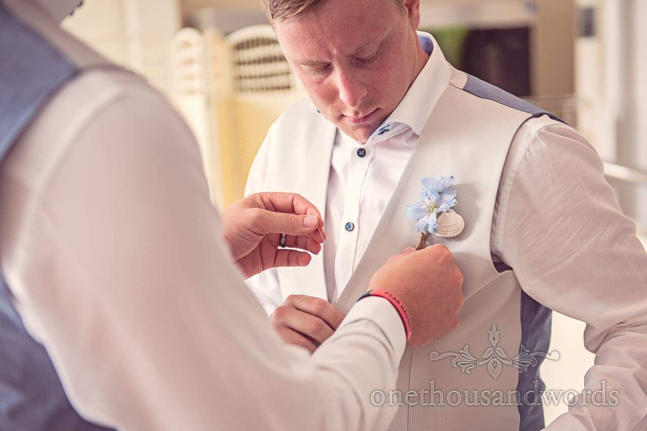 Groomsmen put in buttonholes at seaside theme wedding in Dorset
