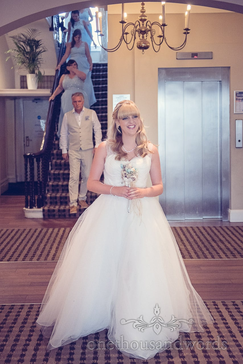 Happy Blonde bride descends stairs at Sandbanks Hotel wedding