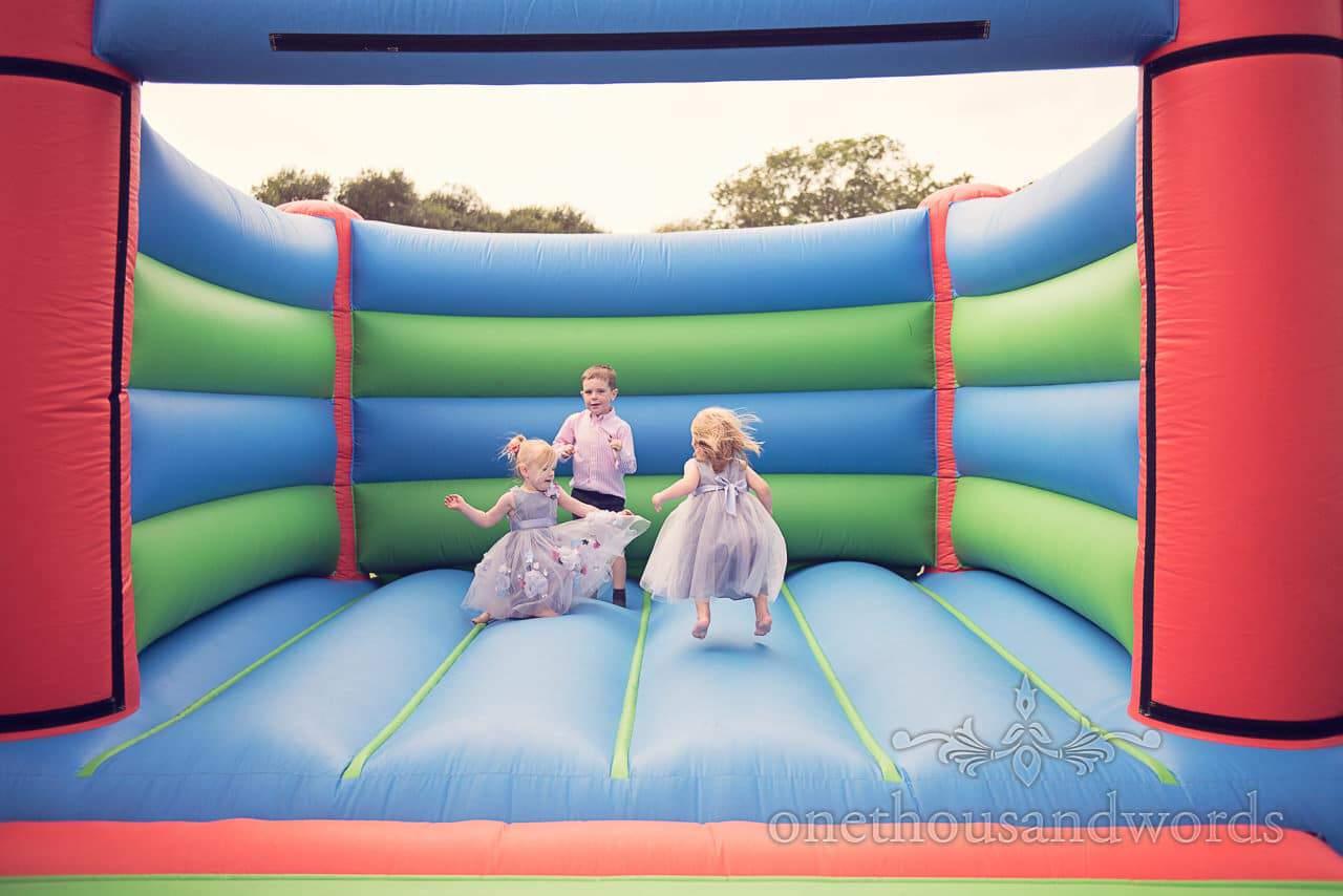 Harmans Cross Wedding photographs of Child guests enjoying bouncy castle