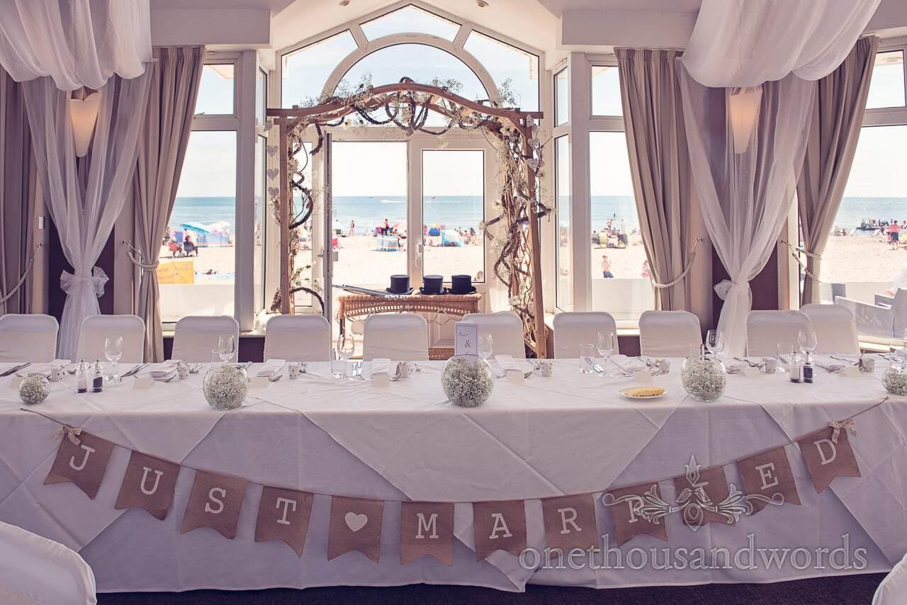 Just married bunting hangs on top table at Sandbanks Hotel Wedding