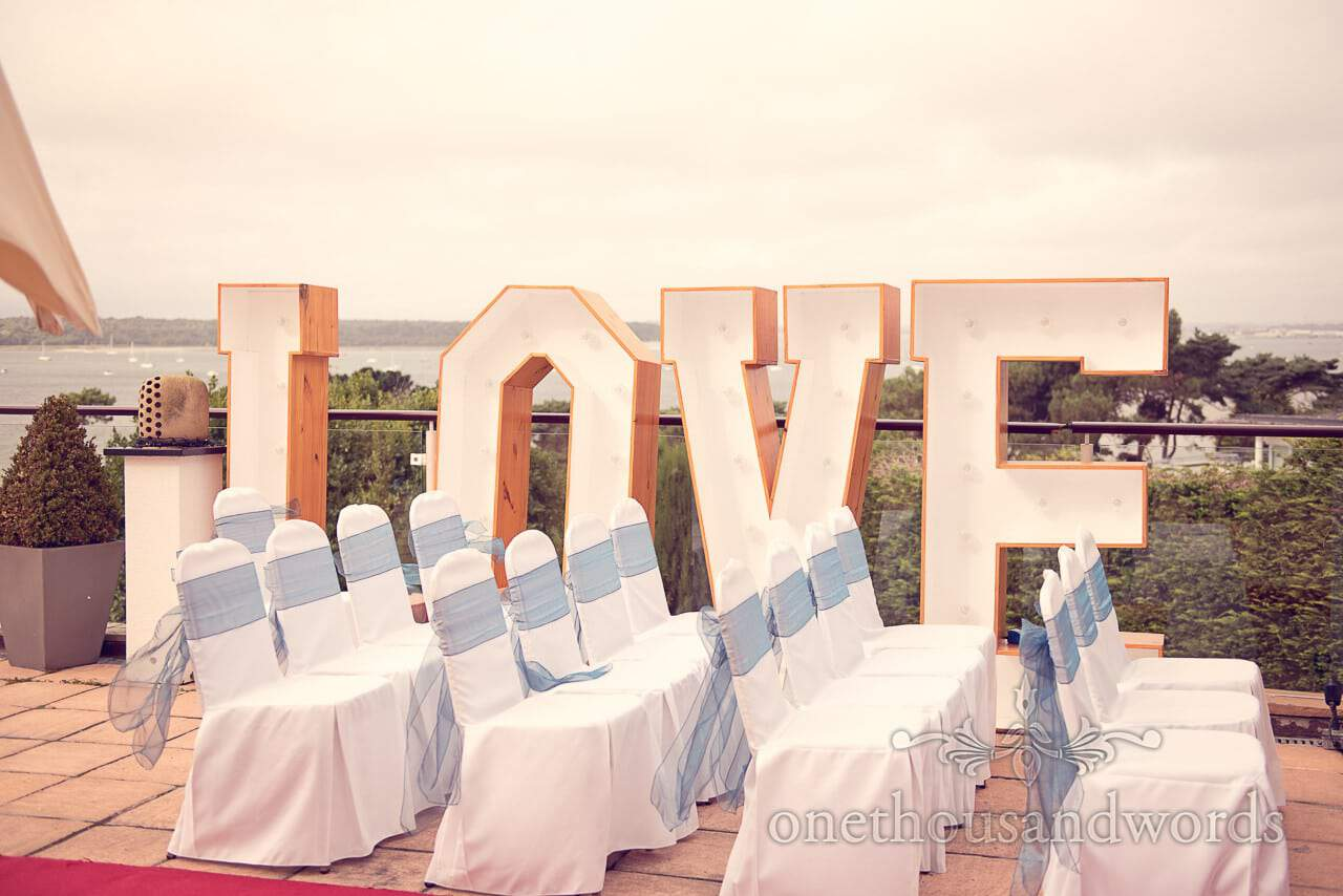 Love letters at chairs with blue sashes on sun terrace at Harbour Heights wedding