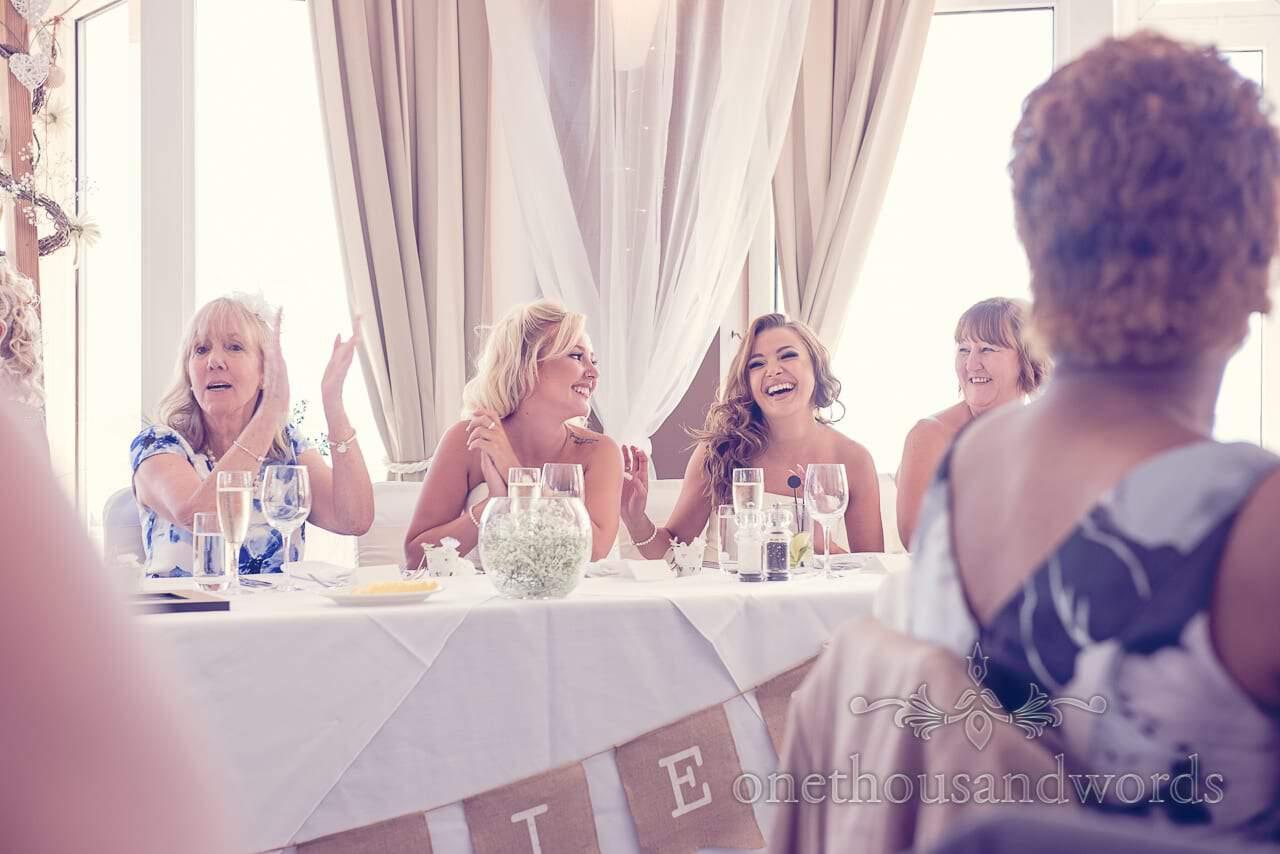 Mother of bride and bridesmaids applaud wedding speeches at Sandbanks Hotel