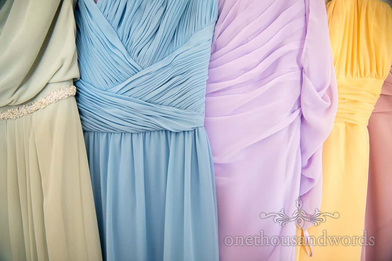 Multi coloured pastel bridesmaid dresses hanging on wedding morning