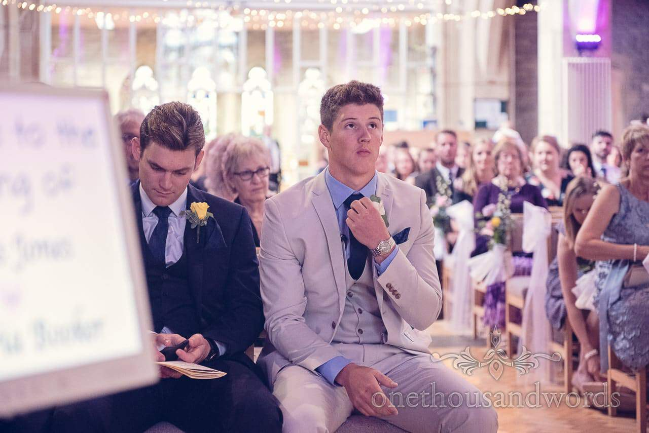 Nervous groom adjusts his tie in Church under fairy lights before wedding ceremony