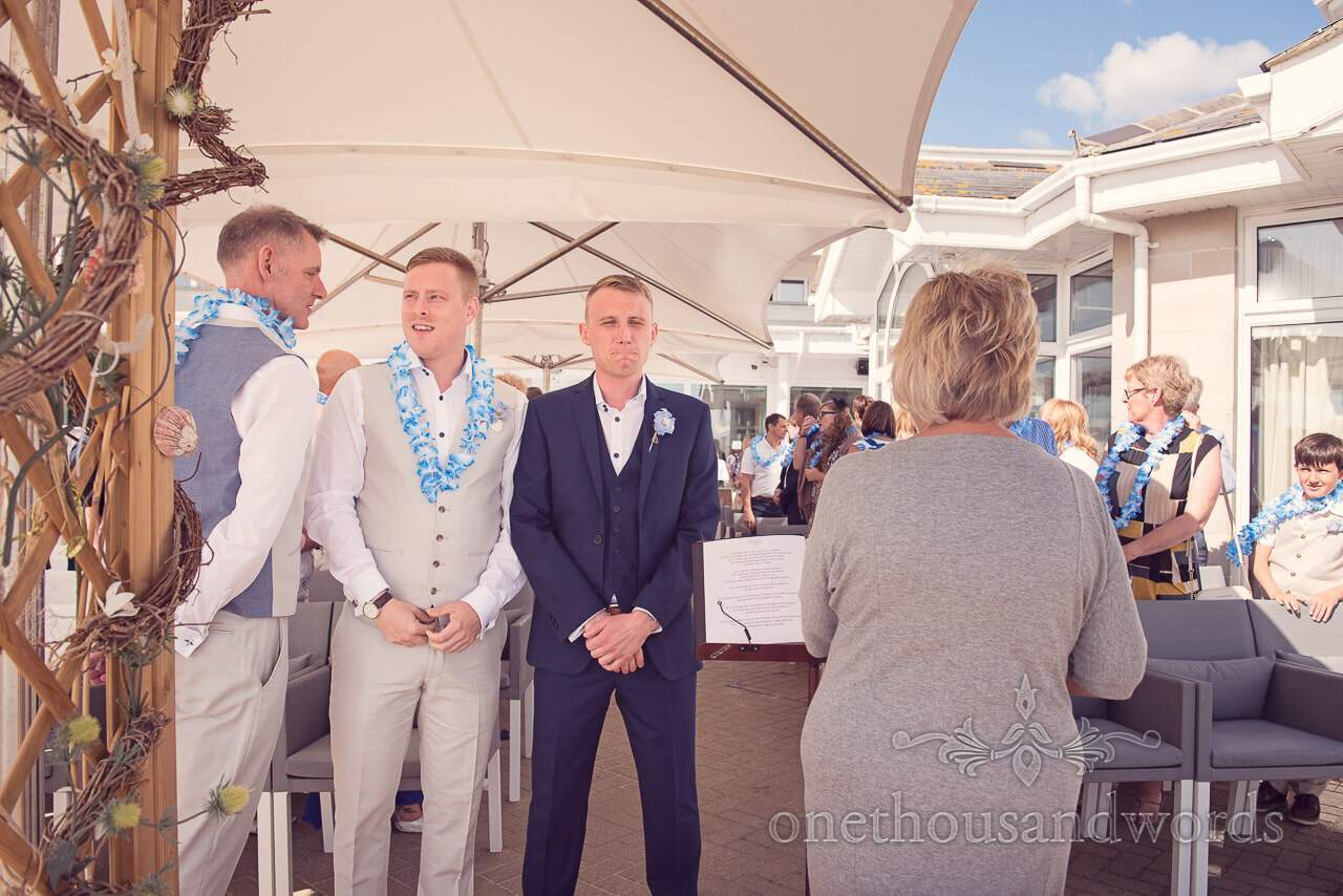 Nervous groom waits for bride at outdoor seaside theme wedding ceremony