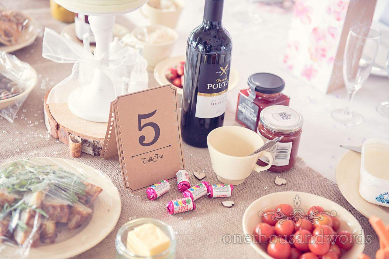 Old film ticket style wedding table number sign with lovehearts and wine