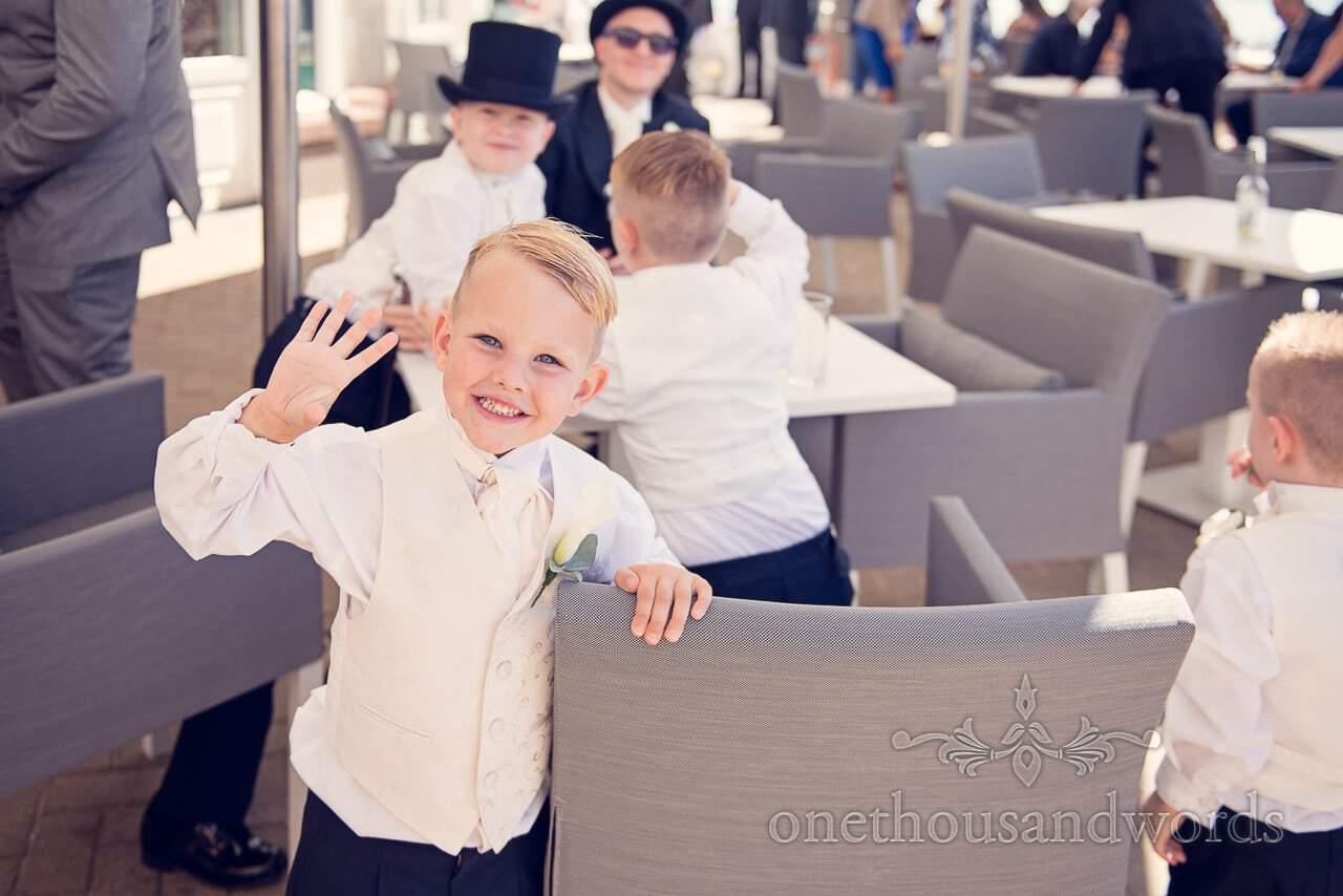Page boy waves to the camera at Sandbanks Hotel Wedding