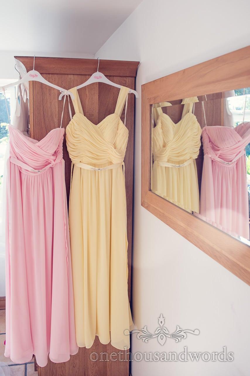 Pastel pink and yellow bridesmaids dresses hanging next to mirror