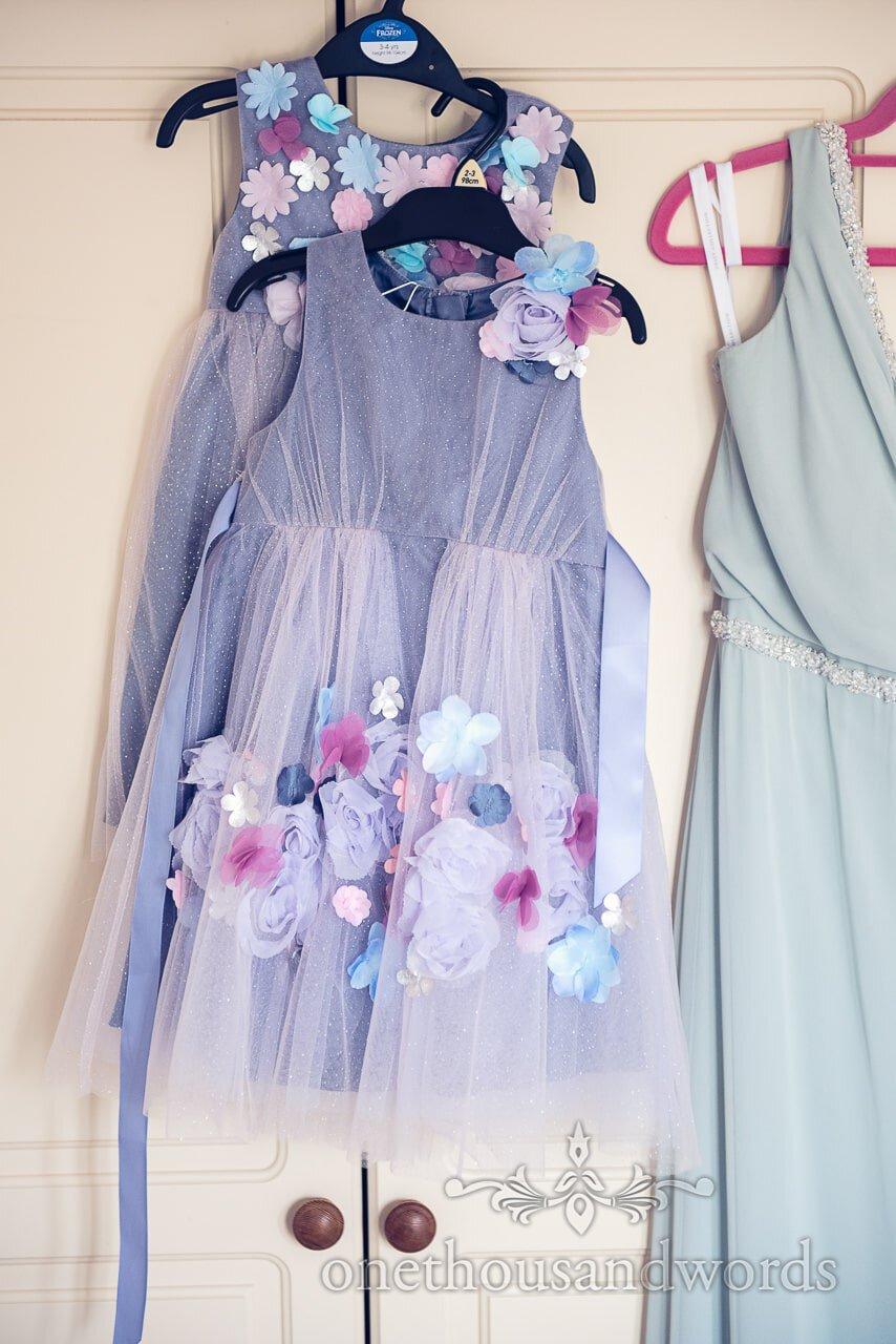 Purple flower girls dresses with pastel coloured flower embellishments