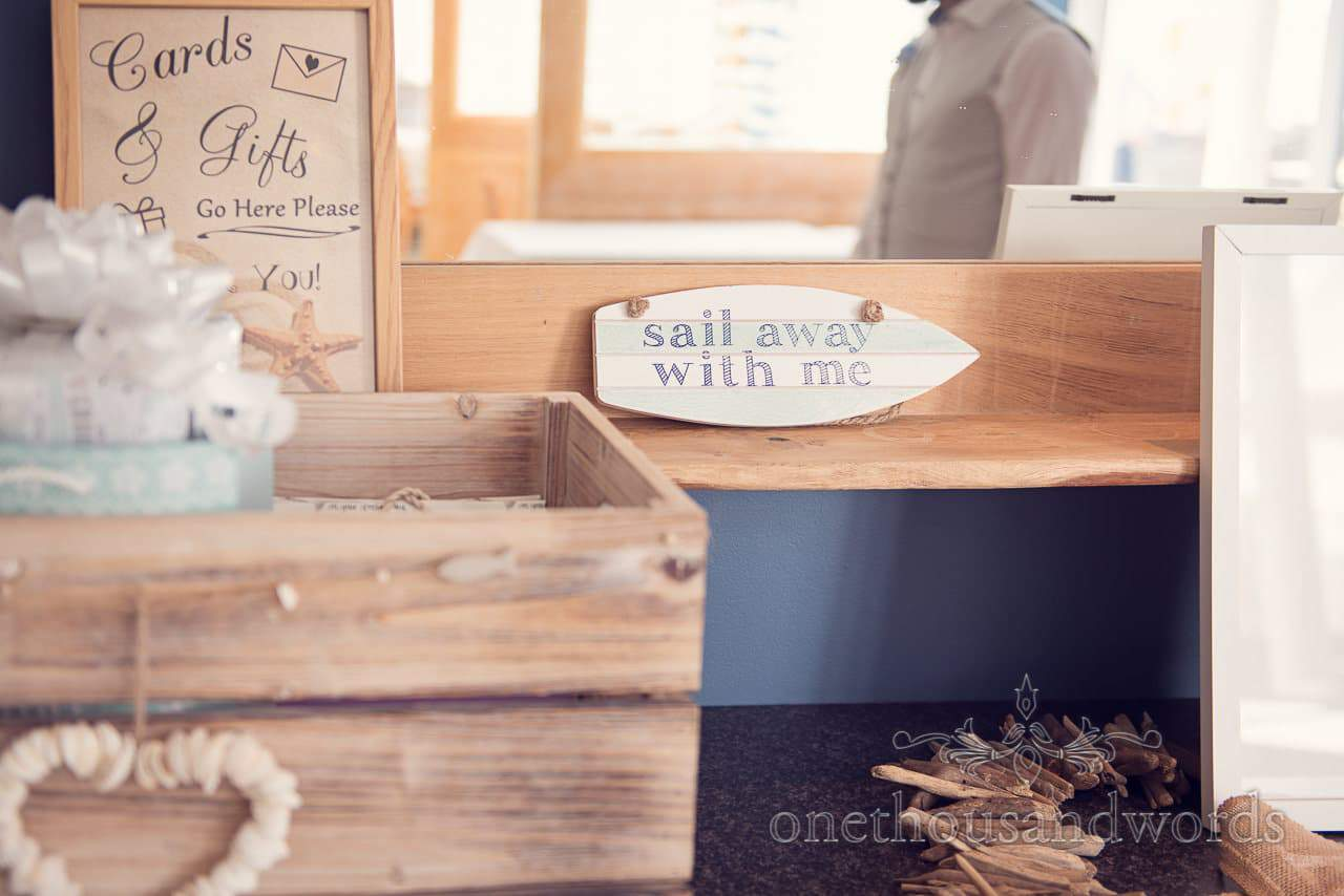 Sail away with me boat shaped sign at seaside theme wedding in Dorset