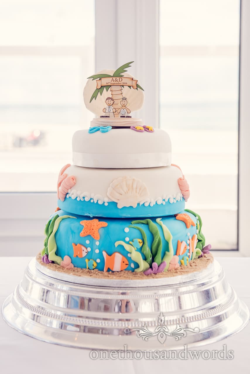 Seaside theme wedding cake with palm tree topper, fish, shells and seaweed