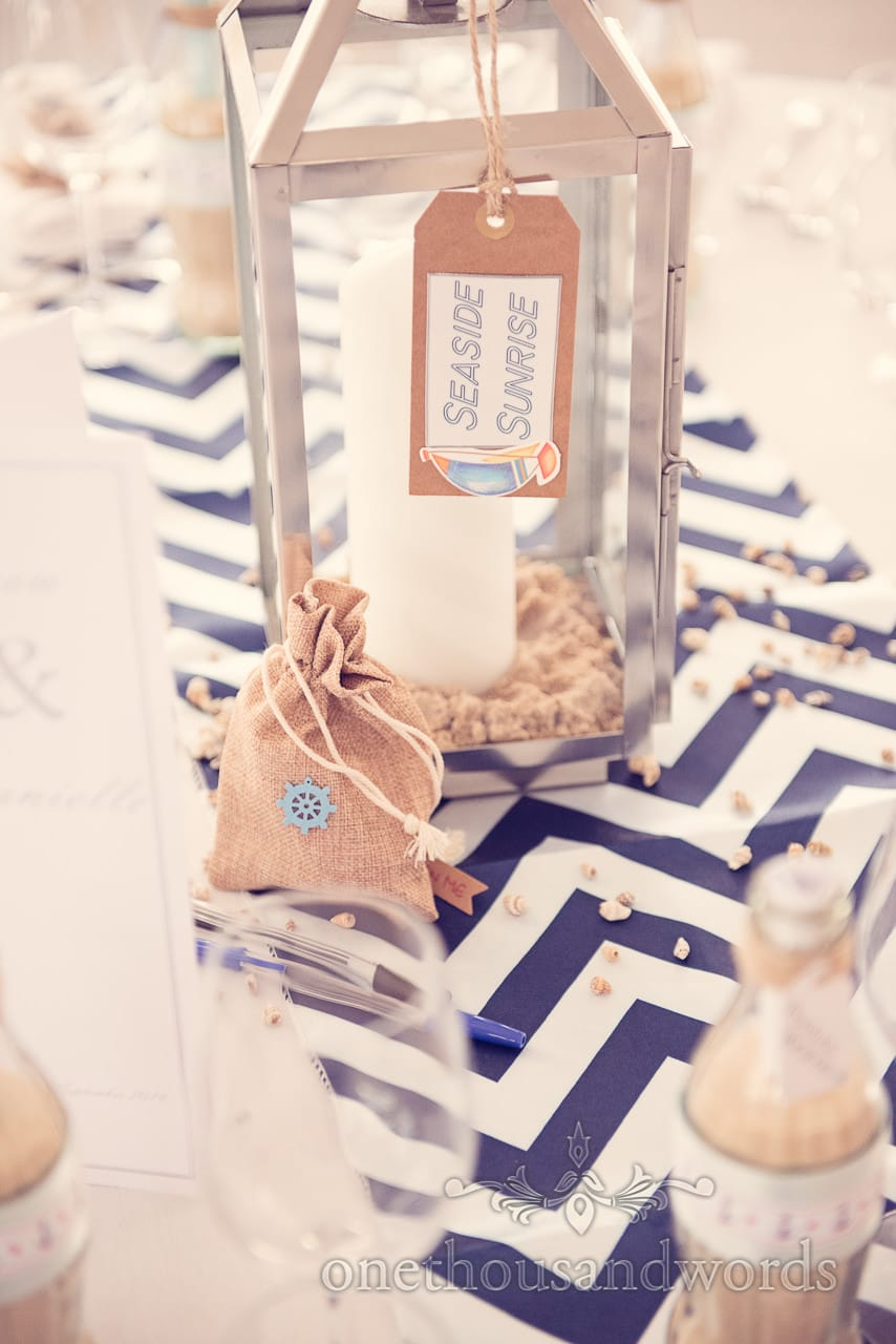 seaside theme wedding cocktail table name with candle in sand and shells