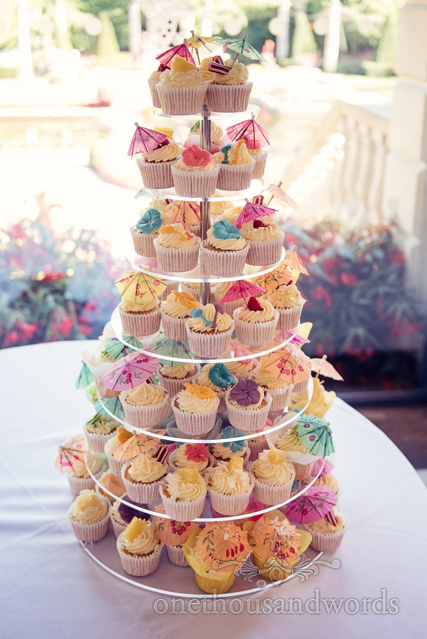 Sea side themed wedding cupcakes with umbrellas, spades, flowers and sweets