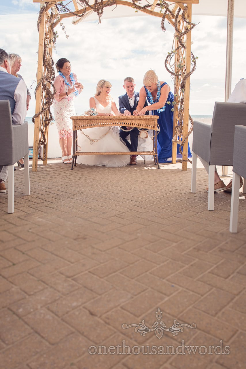 Signing the register at outdoor seaside theme wedding in Dorset